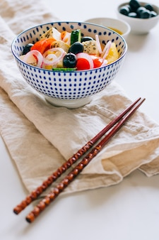 Vegetables salad and olives with chopsticks on marble