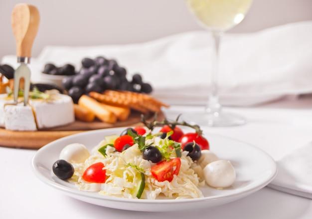 Овощной салат на тарелке, стакан белого вина и тарелка с ассорти из сыра, фруктами и другими закусками.