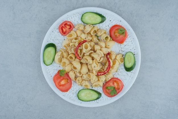 Салат из овощей на белой тарелке с вкусными макаронами на мраморном фоне