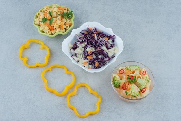 Салат из овощей на белой тарелке с макаронами на мраморном фоне. фото высокого качества