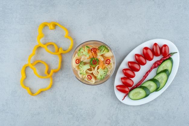 大理石の背景にマカロニと白いプレートの野菜サラダ。高品質の写真