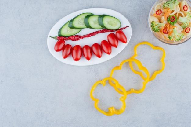대리석 표면에 마카로니와 흰 접시에 야채 샐러드