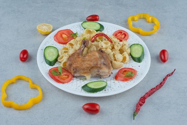 Салат из овощей на белой тарелке с пастой и курицей на мраморном фоне