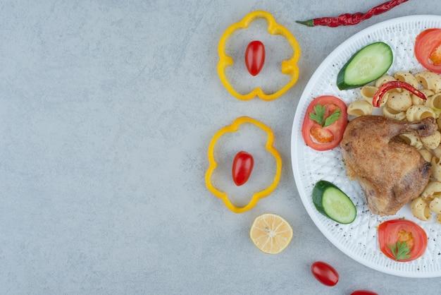 파스타와 대리석 배경에 닭고기와 흰 접시에 야채 샐러드