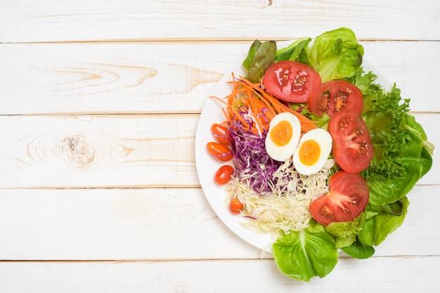 白い木製の背景に野菜サラダ