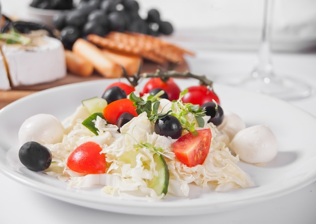 Vegetables salad on the plate, glass of white wine and plate with assorted cheese, fruit and other snacks.