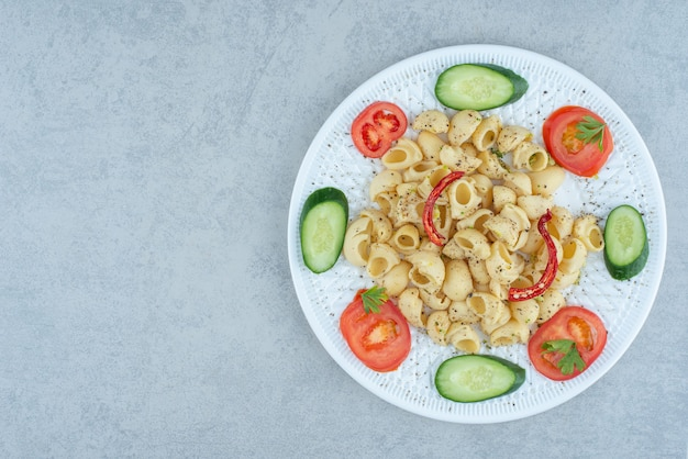 Vegetables salad on white plate with delicious macaroni on marble background