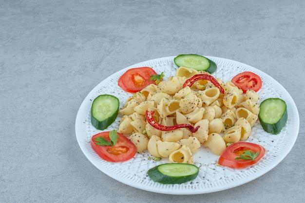 Insalata di verdure sul piatto bianco con deliziosi maccheroni su sfondo di marmo