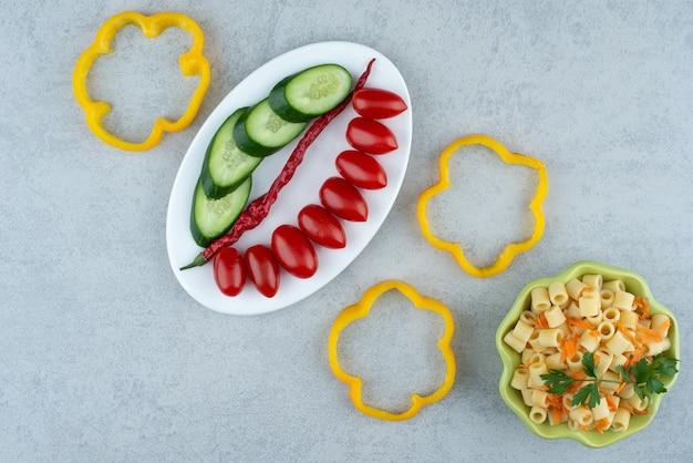 Insalata di verdure sulla zolla bianca con maccheroni su priorità bassa di marmo. foto di alta qualità