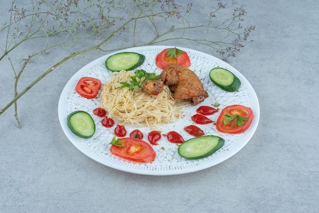 Insalata di verdure sulla zolla bianca con pasta e pollo su fondo di marmo