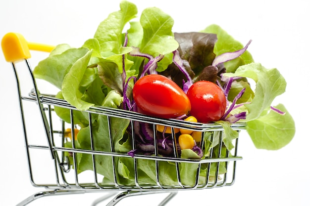 Vegetables in the shopping cart on white background