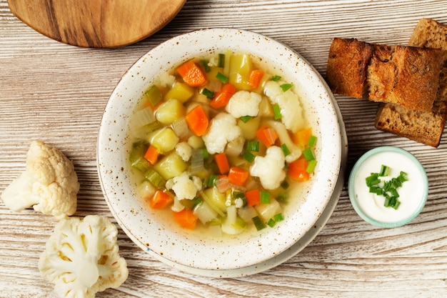 Vegetables soup with cauliflowers, onion, celery, carrots, tomatoes, potatoes, peas, zucchini.