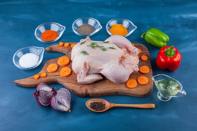 Vegetables, spices, oil, spoon and raw whole chicken on a cutting board on the blue surface