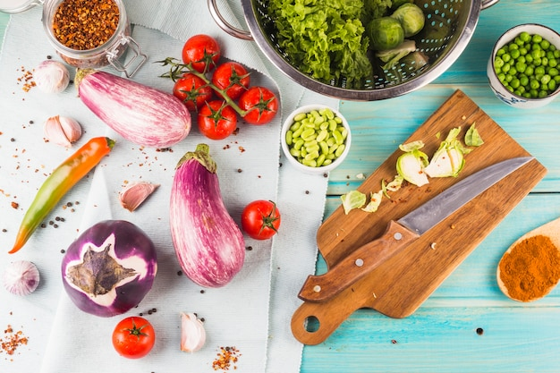 Vegetables and spices with chopping board and knife on wooden table