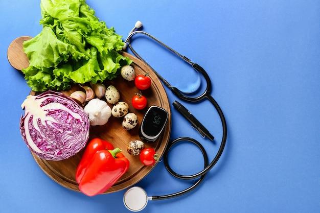 Овощи, стетоскоп, ланцетная ручка и глюкометр. концепция диабета