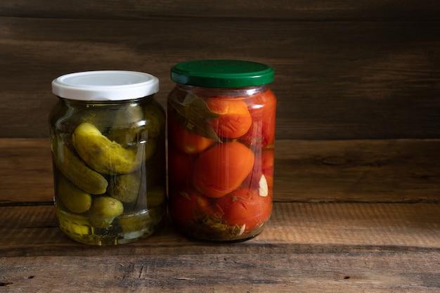 暗い木製の背景に缶詰の野菜トマトとキュウリ。食品ストックの概念