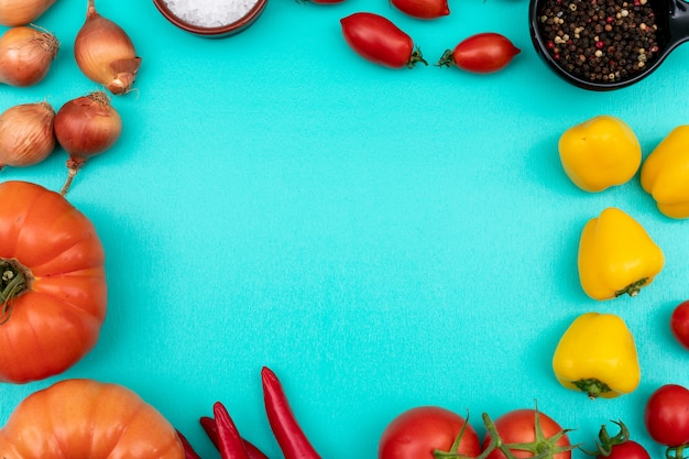 Vegetables tomatoes onion pepper top view on blue surface
