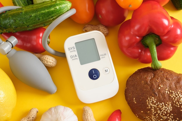 노란색 배경 복사 공간에 있는 야채 안압계, 디지털 혈압계. 적절하고 건강한 영양 개념