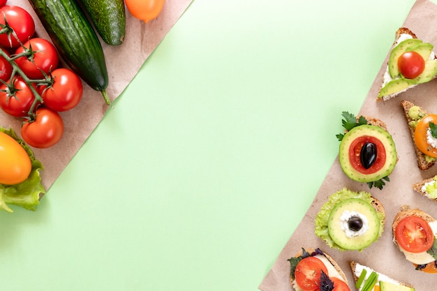 Vegetables and vegetarian sandwiches are lying on wrapping paper pieces on green background with copy space.
