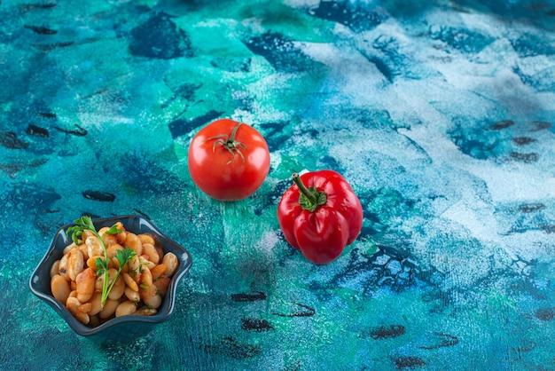 Овощи с миской печеной фасоли на синем столе.