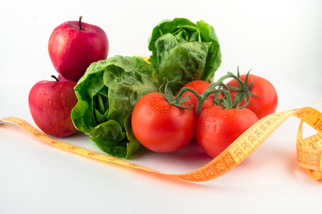 Vegetables with measuring tape on table