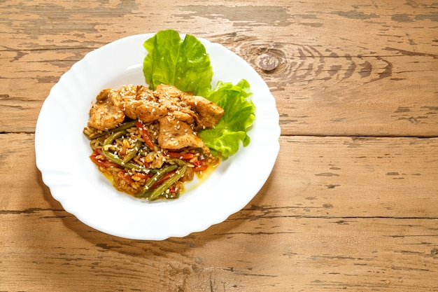 Vegetables with rice and chicken in a pan-asian sauce with sesame seeds on green salad leaves on a wooden table in a plate