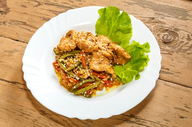 Vegetables with rice and chicken in sauce and sesame seeds on salad leaves on a wooden table in a plate