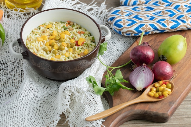 Vegetables on wooden board with bowl of noodles