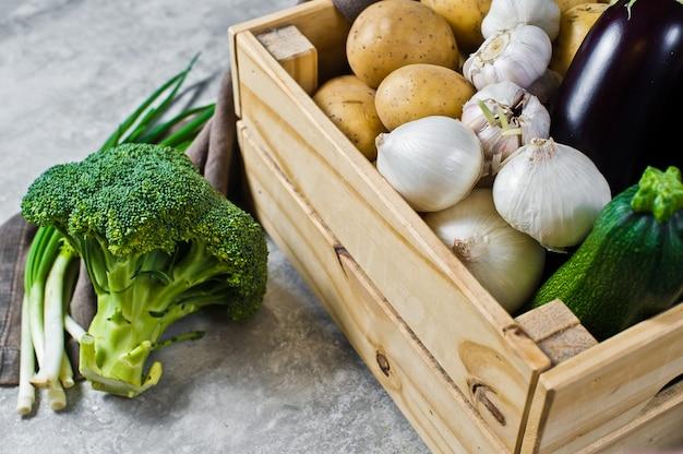 Vegetables in a wooden box: potatoes, onions, garlic, eggplant, zucchini, broccoli, green onions.