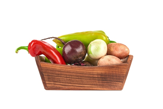 Vegetables in wooden tray on white.