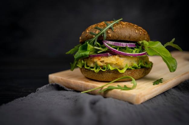 ベジタリアンアメリカ料理。魚、ルッコラ、きゅうりのハンバーガー。黒の背景にハンバーガー。
