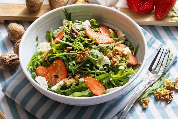 Вегетарианский и полезный салат из зеленых натуральных сырых и свежесрезанных проростков рукколы и листьев капустных со свежей клубникой