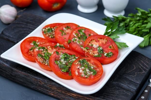 にんにく、パセリ、暗い表面のプレートに蜂蜜とオリーブオイルをまとったトマトのベジタリアン前菜、クローズアップ、水平形式