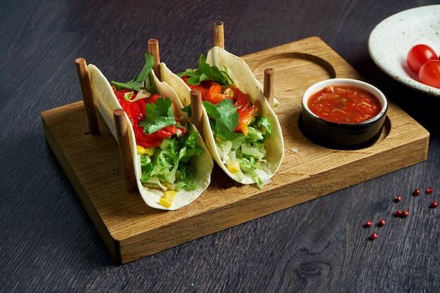 Вегетарианские аппетитные мексиканские тако с помидорами и болгарским перцем, капустой, луком и петрушкой на специальных подставках. традиционная мексиканская кухня