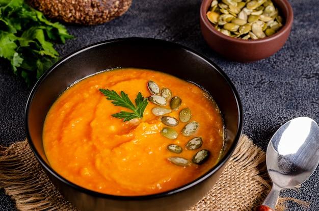 Вегетарианский осенний крем-суп из тыквы и моркови с семенами и петрушкой на темной поверхности