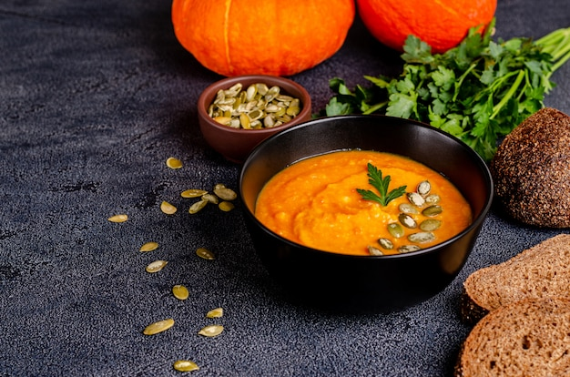 Vegetarian autumn cream soup of pumpkins and carrots with seeds and parsley on a dark table