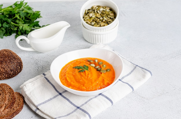 Vegetarian autumn cream soup of pumpkins and carrots with seeds and parsley, flat lay
