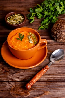 Vegetarian autumn cream soup of pumpkins and carrots with seeds and parsley with copy space, flat lay