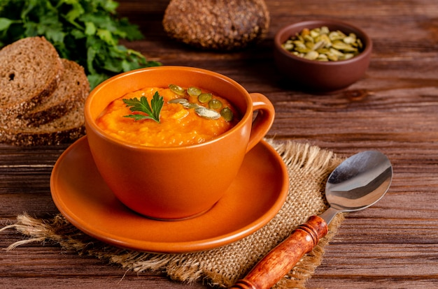 Vegetarian autumn cream soup of pumpkins and carrots with seeds and parsley on a wooden surface with copy space, flat lay