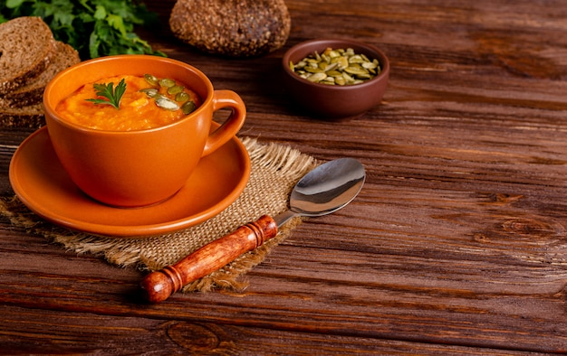 Vegetarian autumn cream soup of pumpkins and carrots with seeds and parsley on a wooden table