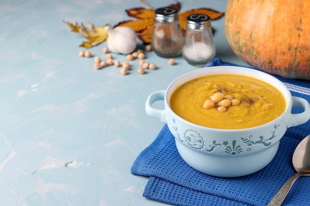 Vegetarian autumn pumpkin cream soup with chickpeas on light blue background, closeup