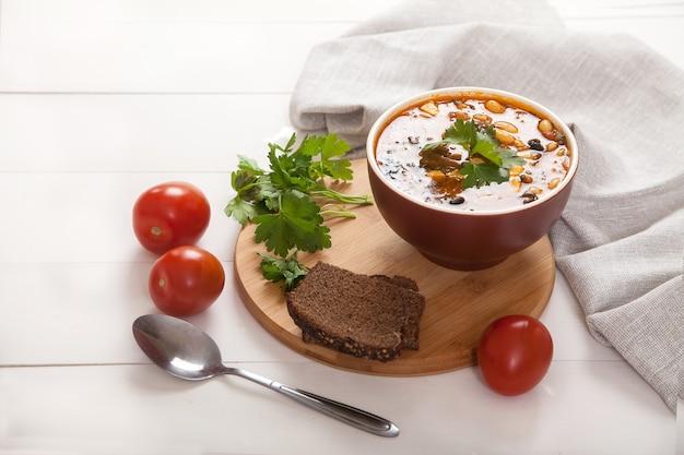 Вегетарианский суп из фасоли и оливок в глиняной посуде, ржаном хлебе, ложке и льняной салфетке на белом деревянном столе.