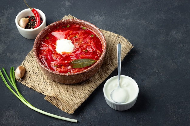 Vegetarian beet red soup - borscht with sour cream on black stone background.