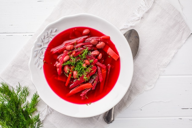 Vegetarian beet soup with beans and vegetables in white plate on white wooden background.