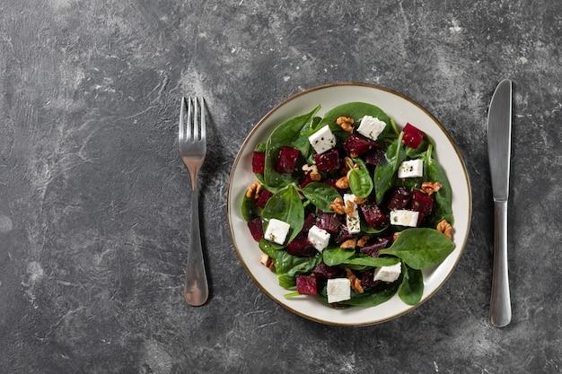 Вегетарианские салаты карпаччо из свеклы со шпинатом, базиликом, оливковым маслом, козьим сыром, грецкими орехами, текстура фон. вид сверху, космос. здоровое питание.
