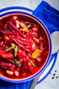 Vegetarian beetroot soup borsch with beans in white bowl