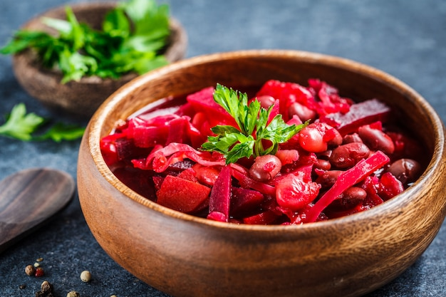 Vegetarian beetroot soup borsch with beans in a wooden bowl on blue surface, healthy vegetarian food concept,