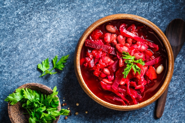 Vegetarian beetroot soup borscht with beans in a wooden bowl on blue surface, healthy vegetarian food concept,