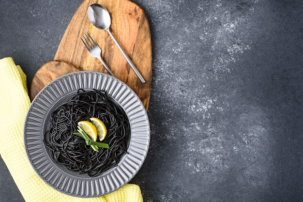 Vegetarian black pasta with cuttlefish ink with lemon slices in gray plate on wooden boards with cutlery on dark gray background with copy space