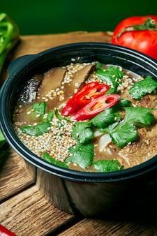 Вегетарианская чаша с рамэн суп, грибы шиитаке, соевое мясо на деревянный поднос в составе со свежими овощами. здоровая пища.
